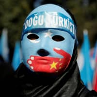 An ethnic Uighur demonstrator wears a mask as she attends a protest against China in front of the Chinese Consulate in Istanbul on Oct. 1. | REUTERS