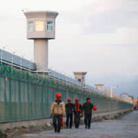Workers walk by the perimeter fence of what is officially known as a vocational skills education center in China's Xinjiang Uighur Autonomous Region in 2018. | REUTERS