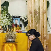A woman prays at an altar with an image of Pham Thi Tra My, who is believed to have been among the 39 people found dead in a truck container last week in the U.K., at her home in Ha Tinh province, Vietnam, Sunday. | REUTERS