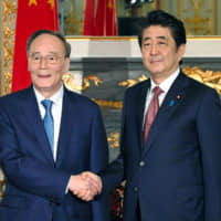 Chinese Vice President Wang Qishan meets with Prime Minister Shinzo Abe at the State Guesthouse in Tokyo on Wednesday. | REUTERS