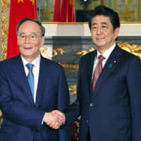 Prime Minister Shinzo Abe and Chinese Vice President Wang Qishan shake hands Wednesday at the State Guesthouse in Tokyo. | POOL / VIA KYODO