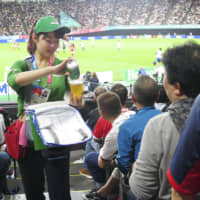 A woman sells beer during a Rugby World Cup match between England and Tonga on Sept. 22 in Sapporo. | KYODO