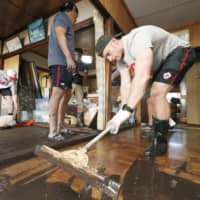 Canadian player Peter Nelson helps to clean up mud inside a house in Kamaishi, Iwate Prefecture, on Sunday, following the cancelation of a Rugby World Cup Pool B match against Namibia due to a powerful typhoon. | REUTERS