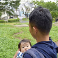 """A father takes a stroll with his child in a park in Yokohama while on paternity leave in July. 
