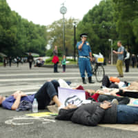 Extinction Rebellion protesters stage a 'die-in' at the entrance to Yoyogi Park on Saturday to call on the government to create a legally binding policy to reduce carbon emissions to zero by 2025. | RYUSEI TAKAHASHI