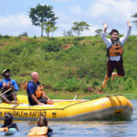Yoma Hiro, an employee at Osaka-based YRGLM Inc., jumps from a rubber dinghy during his vacation in Uganda in March. | COURTESY OF YRGLM INC. / VIA KYODO