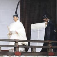 Emperor Naruhito walks in a shrine at the imperial palace in Tokyo for a ritual Tuesday morning prior to proclaiming his enthronement later in the day. | POOL / VIA KYODO