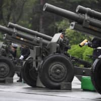 Self-Defense Forces troops prepare to fire ceremonial artillery during a proclamation ceremony marking Emperor Naruhito's ascension to the throne, at a park in Tokyo on Tuesday. | AFP-JIJI