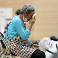 An elderly woman sits in an evacuation center in the city of Tateyama, Chiba Prefecture, on Saturday as Typhoon Hagibis approaches. | KYODO