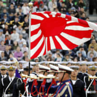 Ground Self-Defense Force members display a Rising Sun flag, regarded by many in South Korea as a symbol of Japan's past militarism, at an event at Camp Asaka in Saitama Prefecture last year. | KYODO