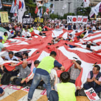 Protesters tear holes in a Rising Sun flag in front of the Japanese Embassy in Seoul on July 20. | KYODO