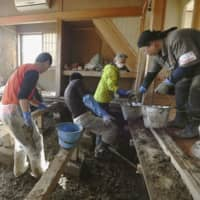 Volunteers remove mud from underneath the floor of a house in the city of Nagano on Sunday. | KYODO