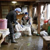Volunteers help clean a house hit by powerful Typhoon Hagibis on Thursday in Motomiya, Fukushima Prefecture, on Thursday.   KYODO