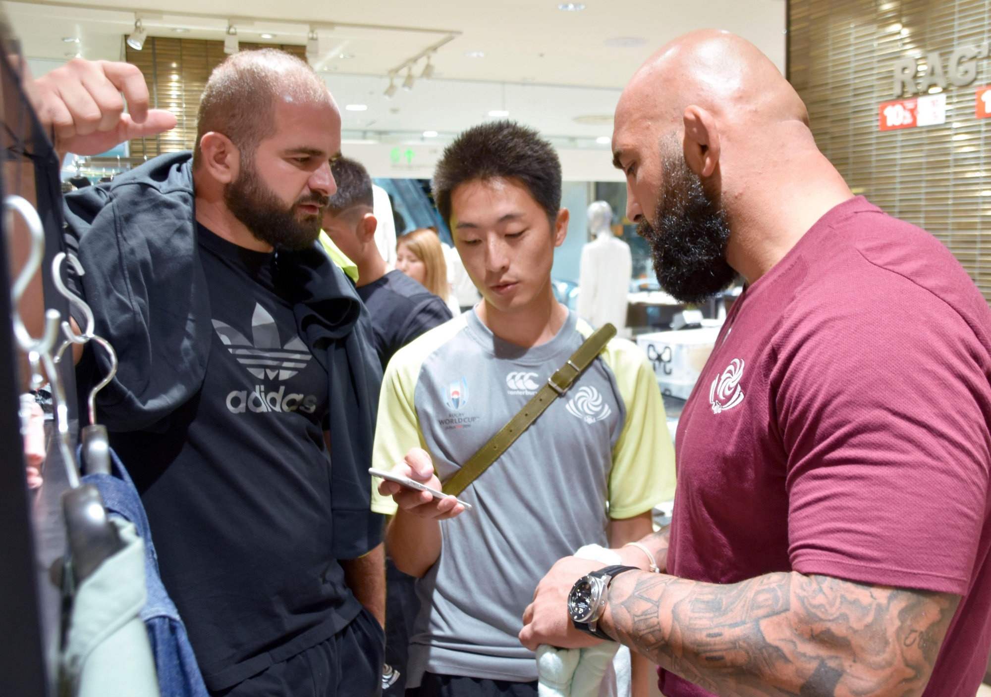 Hayate Sotome interprets for members of Georgia's national rugby team as they shop in Nagoya last month during their stay in this country for the Rugby World Cup. | KYODO
