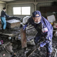 Volunteers on Wednesday help clean out a house damaged by giant Typhoon Hagibis in the city of Nagano. | KYODO
