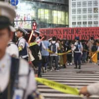 Revelers, some in Halloween costumes, are blocked by police at the famed scramble crossing in Tokyo's Shibuya Ward on Saturday night. | KYODO