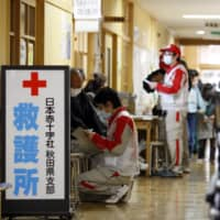 Members of the Japanese Red Cross Society work at a medical booth at an evacuation center in Rikuzentakata City, Iwate Prefecture, in April 2011, a month after a major earthquake struck the region. | BLOOMBERG