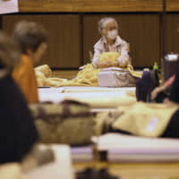 Evacuees from Typhoon Hagibis take shelter at an elementary school gym in Kawagoe, Saitama Prefecture, on Monday. An evacuation center in Taito Ward, Tokyo, turned away two homeless people on Saturday as the storm bore down on the capital. | AP