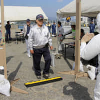 Residents of Ikata, Ehime Prefecture, undergo radiation checks after arriving in Usuki, Oita Prefecture, during a disaster drill Wednesday at Ikata nuclear power plant. | KYODO