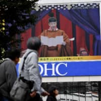 An outdoor screen in the Shinjuku district of Tokyo displays a live broadcast of Emperor Naruhito proclaiming his accession to the chrysanthemum throne on Tuesday.   AFP-JIJI