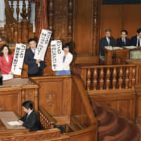 Upper House members opposed to a bill to allow casinos to open in Japan hold up banners urging the government to use taxpayer money for other purposes, during an Upper House plenary session in July 2018. | KYODO