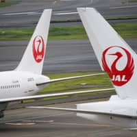Japan Airlines aircraft are parked at Haneda Airport in Tokyo in May. | BLOOMBERG