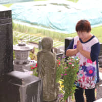 Mieko Okubo prays in the village of Iitate, Fukushima Prefecture, in August at the grave of her father-in-law, Fumio, who killed  himself in April 2011 after the government issued an evacuation order following the triple meltdown at the Fukushima No. 1 nuclear power plant. | KAHOKU SHIMPO