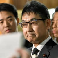 Katsuyuki Kawai speaks to reporters at the Prime Minister's Office in Tokyo after handing in a letter of resignation as justice minister. | KYODO