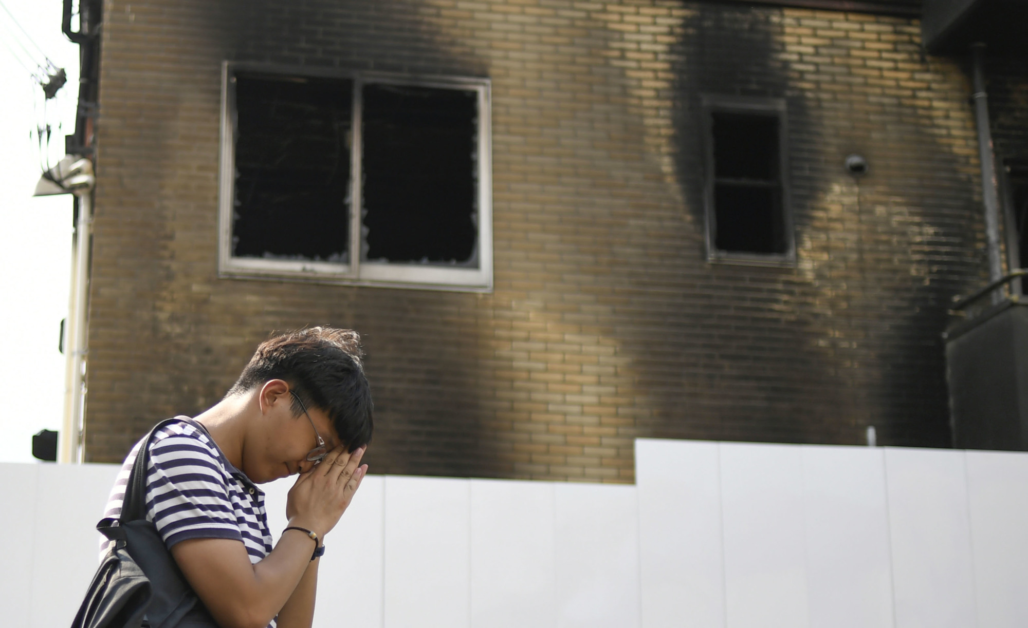 Standing outside the torched building, a man offers prayers for victims of the July 18 arson attack on Kyoto Animation's studio in the city's Fushimi Ward later in the month. | KYODO