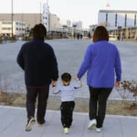A lesbian couple walk with their child in the city of Saitama in January. They found a sperm donor via the internet. | KYODO