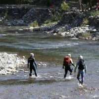 Yamanashi Prefectural Police officials search Wednesday along the Doshi River in Sagamihara, Kanagawa Prefecture, for traces of a missing 7-year-old girl. | KYODO