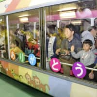 Passengers chosen by lottery to ride on the monorail's last run at Ueno Zoo in Tokyo wave on Thursday. | KYODO