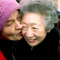 A Bosnian Serb from Sarajevo cries while hugging U.N. refugee chief Sadako Ogata at a camp in a northern suburb of Belgrade on Dec. 6, 1997. | REUTERS / VIA KYODO