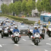 Cars and motorcycles make their way down a road in Tokyo on Sunday during a parade rehearsal Oct. 22 to mark Emperor Naruhito's enthronement. | KYODO