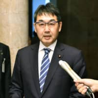 Justice Minister Katsuyuki Kawai speaks to reporters Friday at the Diet about the pardons to be granted as part of the imperial enthronement ceremony on Tuesday. | KYODO