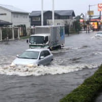 A street is flooded and vehicles are partially submerged due to torrential rain on Friday in Narita, Chiba Prefecture. | AP