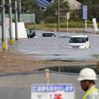 Vehicles are submerged in water Saturday in the city of Sakura, Chiba Prefecture, following torrential rain the previous day.   KYODO