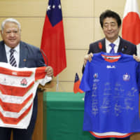Samoan Prime Minister Tuilaepa Lupesoliai Sailele Malielegaoi and Prime Minister Shinzo Abe pose at the Prime Minister's Office on Wednesday after exchanging Japanese and Samoan national rugby team uniforms.   KYODO