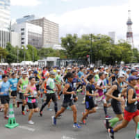 Runners compete in a marathon in Sapporo in August 2018. | KYODO