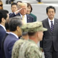 U.S. President Donald Trump salutes alongside Prime Minister Shinzo Abe as they inspect the Japanese Maritime Self-Defense Force helicopter carrier Kaga, docked at the MSDF base in Yokosuka, Kanagawa Prefecture, in May. | KYODO
