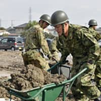 Self-Defense Forces personnel remove mud from junior high school grounds in Sano, Tochigi Prefecture, on Oct. 17, after the area was hit by Typhoon Hagibis. | KYODO