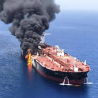 An oil tanker burns in the Gulf of Oman on June 13 after it was attacked near the strategic Strait of Hormuz. | ISNA / AP / VIA KYODO