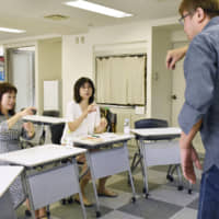 Takeshi Sunada (right) teaches the language called International Sign to a class in Shinjuku Ward, Tokyo, on Oct. 5. | ??
