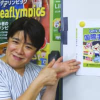 Sachiyo Yoshino, director of the Japanese Federation of the Deaf, introduces a book titled 'Let's Try Kokusai Shuwa' (International Sign) in Tokyo on Oct. 8. | KYODO