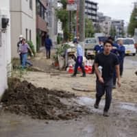 Workers struggle to clean mud and garbage left after the flood in the Kami-Maruko district near JR Musashikosugi Station in Kawasaki, Kanagawa Prefecture, on Tuesday. The flood is believed to have been caused by back-streaming from underground drains connected to the Tama River due to Typhoon Hagibis. | REIJI YOSHIDA