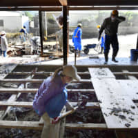 Volunteers clean up mud on Monday in a house in the town of Marumori, Miyagi Prefecture, that was damaged by Typhoon Hagibis earlier this month. | KYODO