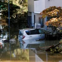 A car is seen partially submerged in a flooded residential of Kawasaki near the Tama River in Kawasaki on Sunday after Typhoon Hagibis hit the area. | REUTERS