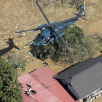 A rescue helicopter flies over flooded houses in the town of Marumori, Miyagi Prefecture, Sunday. | KYODO