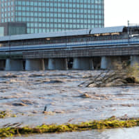 The swollen Tama River is shown in Tokyo on Sunday following heavy rainfall Saturday night during the passage of Typhoon Hagibis. | REUTERS