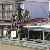People are rescued by Self-Defense Forces personnel from the roof of a submerged house Sunday in the city of Kakuda, Miyagi Prefecture. | KYODO